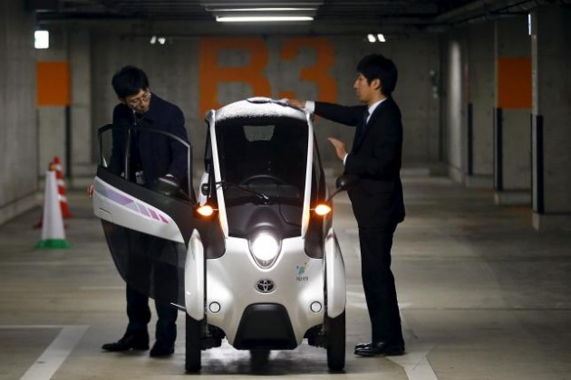 Staff members clean Toyota i-Road electric vehicle in Tokyo