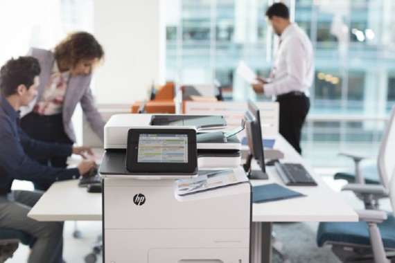 Office workers looking over prints from the HP PageWide Enterpri